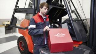 Service-Techniker mit Service-Kit vor Gabelstapler